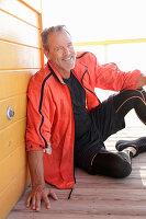 Grauhaariger Mann in schwarzer Sportbekleidung und roter Jacke