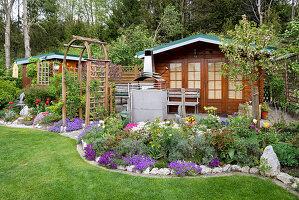 Schrebergarten mit Gartenhaus, Gerätehaus, Staudenbeet und Rosenbogen