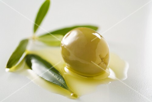 Green olive with olive oil and olive leaves (close-up)