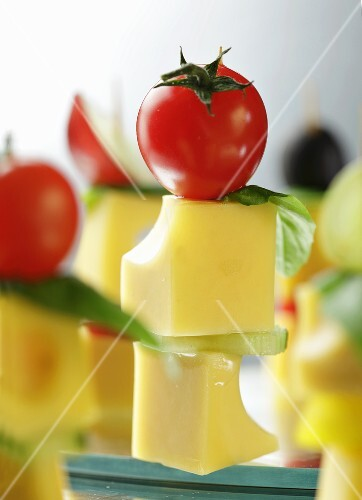 Cubes of cheese on sticks with cherry tomatoes