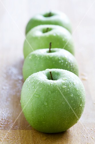 Four green, freshly washed apples