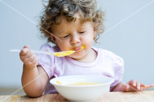 A little girl eating baby food