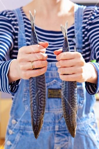 A woman holding two mackerel