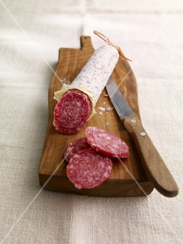 A salami on a chopping board, sliced
