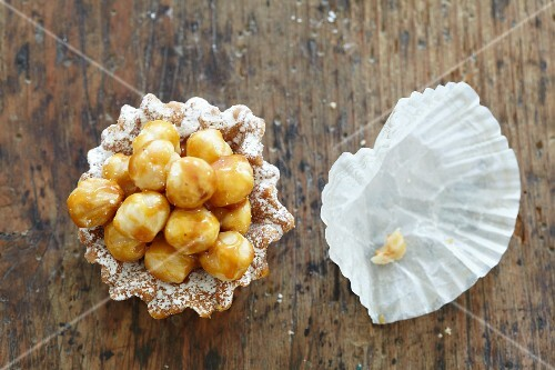 A macadamia nut tartlet and an empty paper case