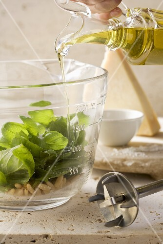 Pouring olive oil on basil leaves and pine nuts