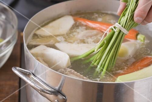 Suppengemüse in einen Topf geben
