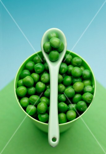 A bowl of peas and a plastic spoon