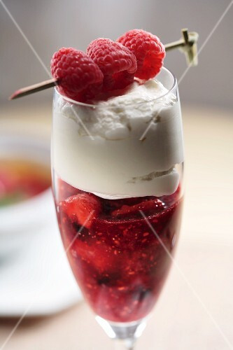 Strawberry dessert with cream garnished with skewered raspberries