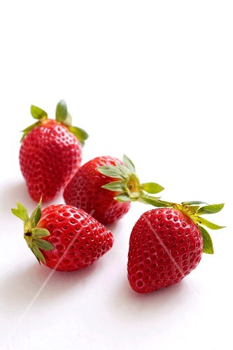 Five strawberries on a white surface