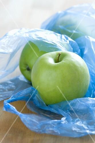 Green apples in plastic bags
