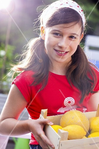 A girl holding a crate of citrus fruits