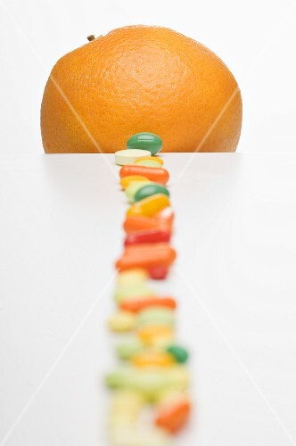 Vitamin tablets and an orange