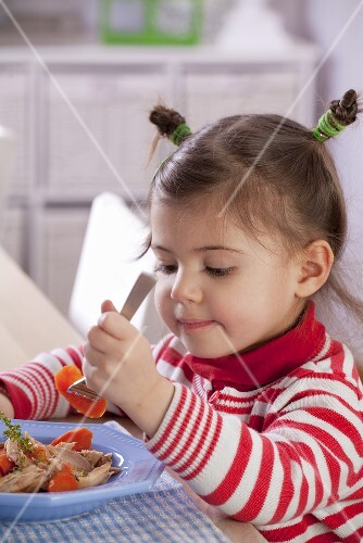 A little girl eating chicken and carrots