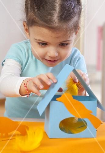 A little girl making a paper bird house
