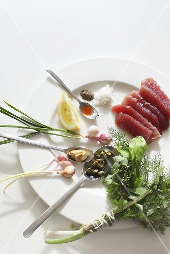 Raw tuna, a bunch of herbs, capers and spring onions