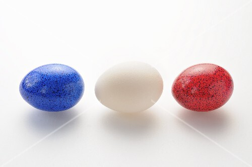 A white egg between two coloured eggs