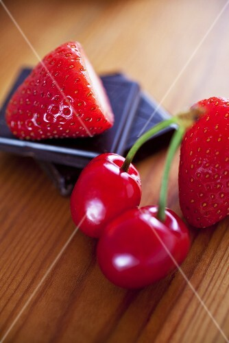 Pieces of chocolate with cherries and strawberries