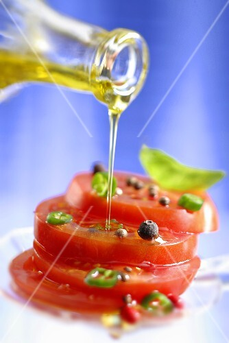 Spiced tomatoes being drizzled with olive oil