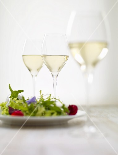 Mixed leaf salad with edible flowers and glasses of white wine