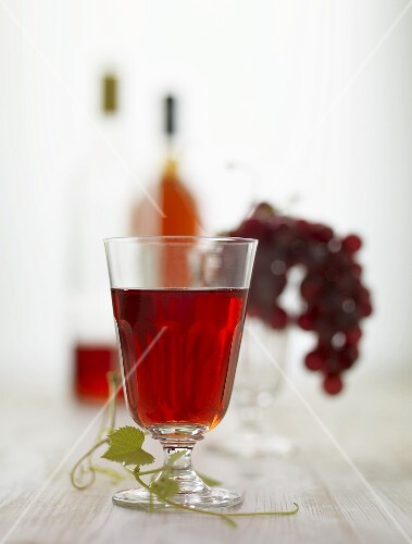 A glass of red wine, red grapes and bottles of red wine