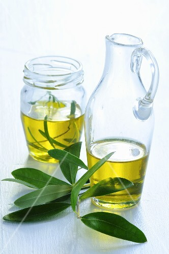 Olive oil in a carafe and in a screw-top jar with olive sprigs