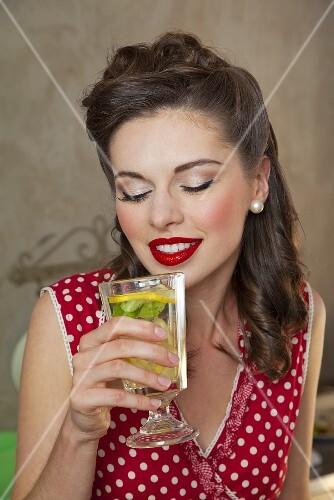 Mädchen im Retro-Look trinkt Zitronenlimonade