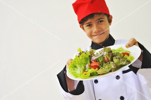 A boy dressed as a chef holding a plate of salad