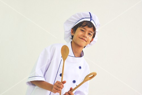 A boy dressed as a chef holding wooden spoons