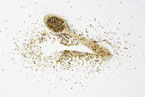 Dried oregano on a spoon and next to it