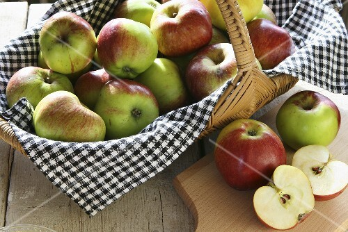 A basket of organic apples and sliced apples on a board