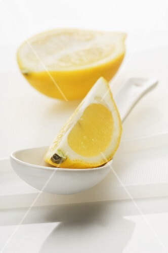 A lemon wedge on a spoon with half a lemon in the background