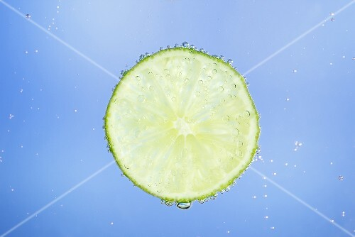 A slice of lime in blue water with air bubbles