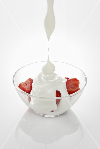 Yogurt dripping onto strawberries in a glass bowl