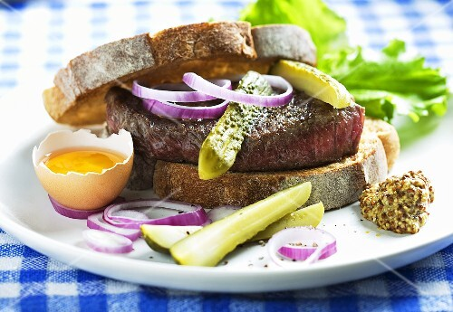 A beef sandwich with gherkins, egg, onion and mustard