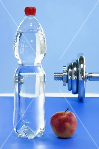 A bottle of mineral water, an apple and a dumbbell