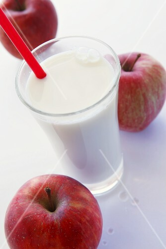 A glass of milk with a straw and three red apples