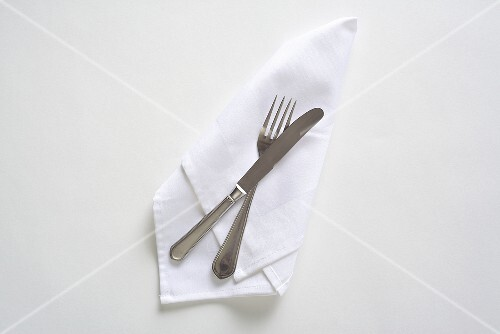 Cutlery on a white napkin, seen from above