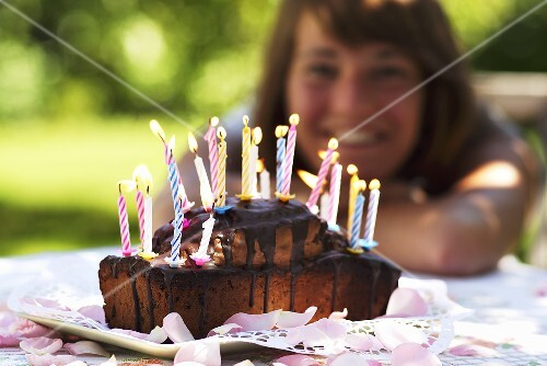 A birthday cake with burning candles and a young woman in the background