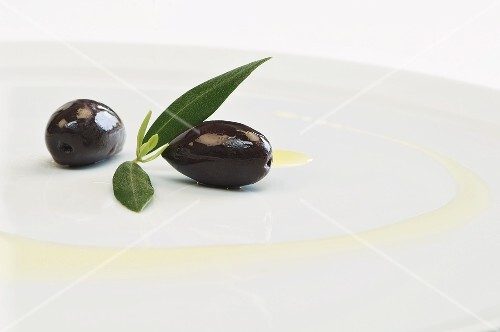 Kalamata olives with leaves and olive oil on a plate