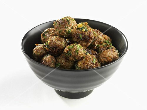 A bowl of meatballs with herbs