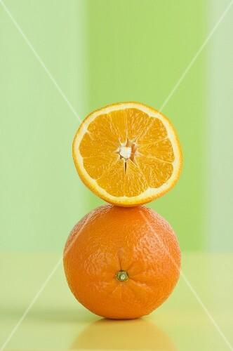 An orange half on top of a whole orange