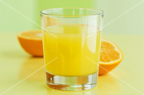 A glass of orange juice with orange halves behind it