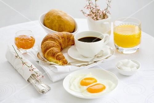 Breakfast with coffee, fried egg, orange juice and jam