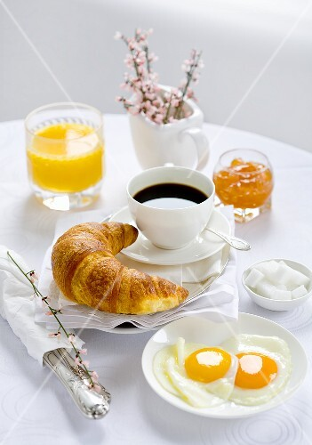 Breakfast with coffee, croissant, fried egg, jam and orange juice