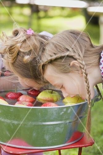 Two girls bobbing for apples
