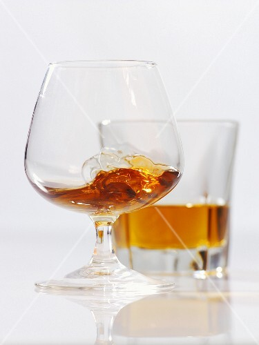 Cognac in a balloon glass and a glass of whiskey