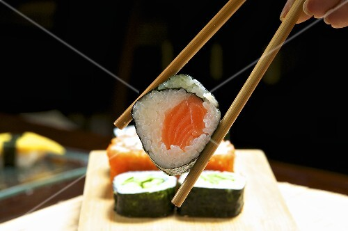 A hand holding a maki sushi in chopsticks
