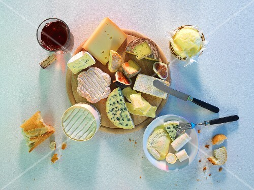 A cheese platter with baguette, figs and red wine