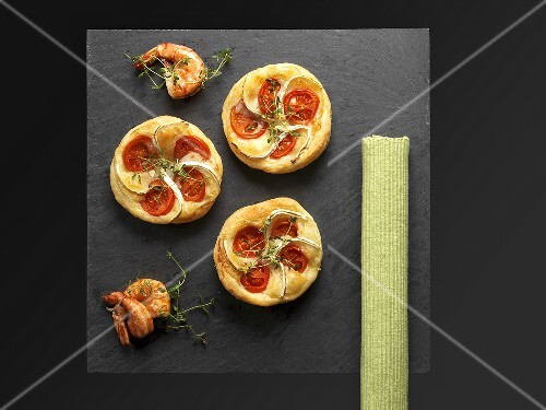 Puff pastry tartlets with goat's cheese and tomatoes on a slate plate